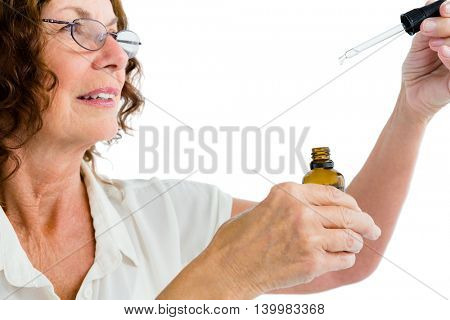 Close-up of mature woman holding dropper with medicine against white background