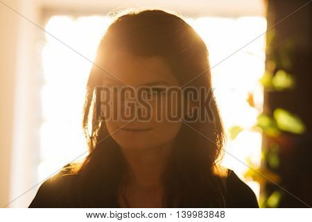 Portrait of a enigmatic young brunette in sunset warm light