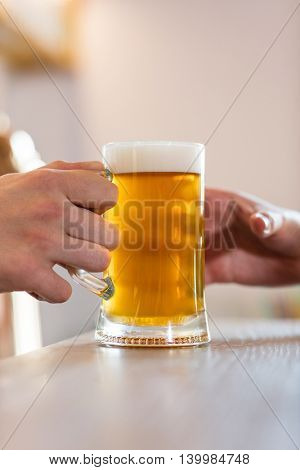 Cropped image of bartender serving beer to customer at bar counter