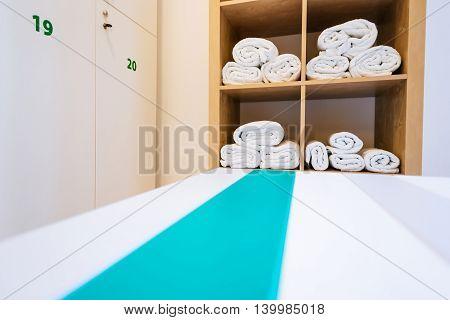 Elegant locker room in a nice gym. Focus on towels in the background.