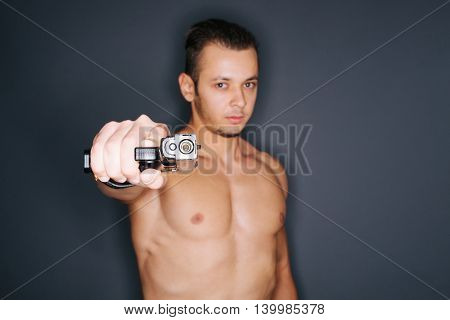 Shirtless man pointing a gun to photographer . Focus on the gun