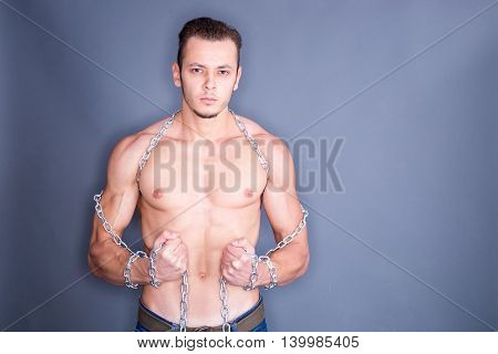 Irritated shirtless man posing with steel chains all around his arms