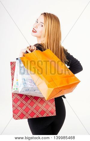 Beautiful smiling woman carrying shopping bags - isolated on white.