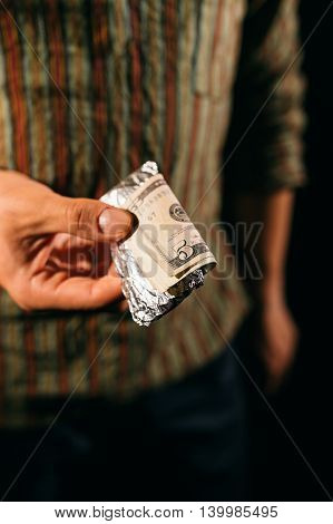 Unknown man holding bills and drugs in hand