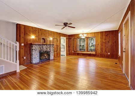 Empty Room With Wooden Pannel Trim, Hardwood Floor And Fireplace