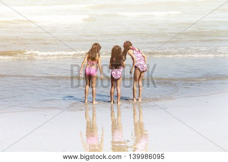 Three little girls standing on the beach in vintage.