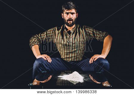 Drug lord with a big pile of cocaine on his table. Illegal activity.
