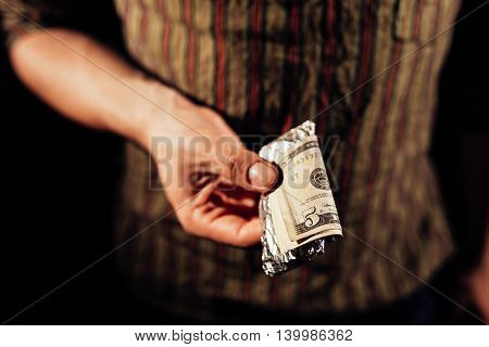 Drug dealer's hand holding a package of cocaine with money on it
