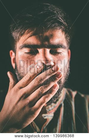 Closeup of a drugged man with eyes closed sniffing cocaine