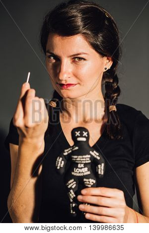 Empowered furious young woman holding a voodoo doll and a needle