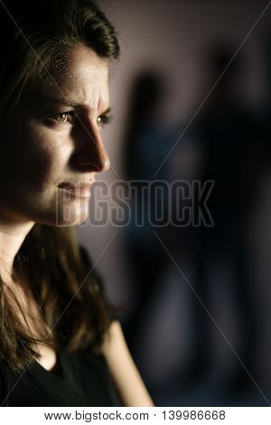 Jealous young woman is looking at a loving couple - couple silhouettes on the background