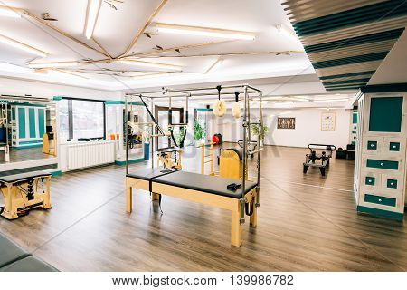 Pilates room with several devices like trapeze table reformers chairs etc