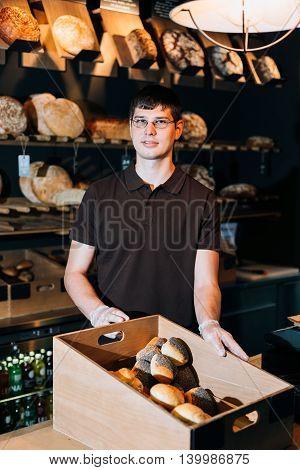 Shopkeeper presents a breadbasket to customer in a bakery