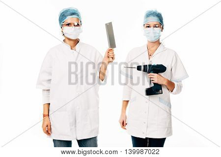 Young female nurses holding a saw and an electric drill