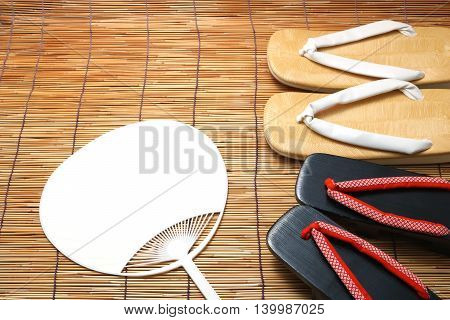 Japanese sandals for men and women and fan on bamboo blinds. Concept of Japanese summer.