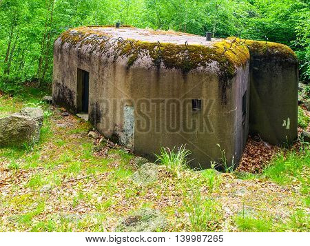 Small concrete military bunker hidden in the forest of czech border area. World War II fortificaion, Czech Republic