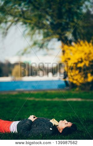 Cheerful woman resting and relaxing lying down on grass in park