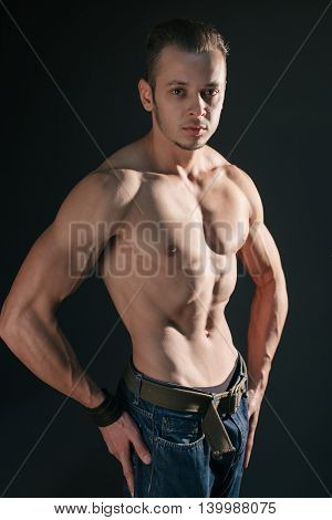 Shirtless serious man with well defined muscles posing at studio