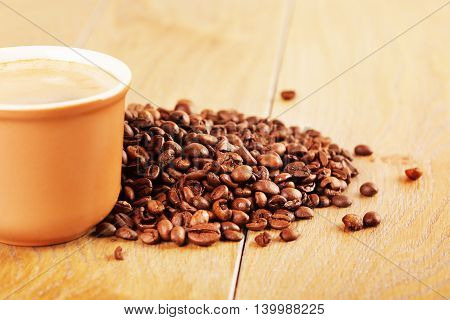 cup of espresso and coffee beans on wooden table