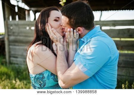 Happy Pregnant Couple At Turquoise Dress Kissing On The Garden