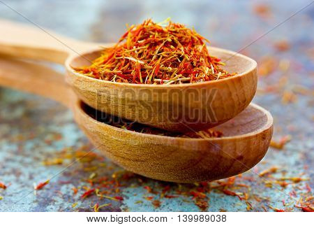 Saffron in wooden spoon close up selective focus