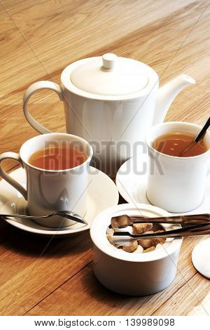 Cup of tea with sugar cubes on the wooden table