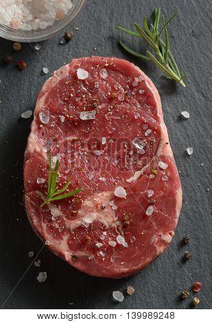 Fresh raw steak with salt and pepper