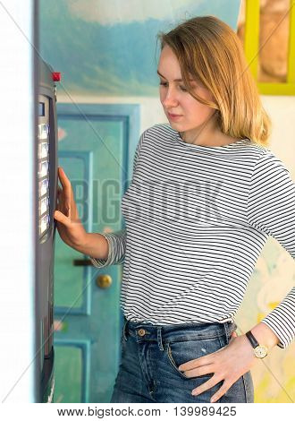 Pretty young woman using coffee vending machine.