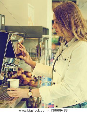 Pretty woman using coffee vending machine. Vintage effect.