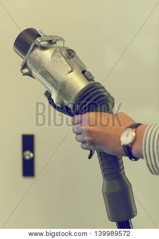 Woman's hand holding power supply for electrocar.
