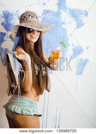 cute bright woman in sunglasses and hat with cocktail in bikini in studio close up tourist, dreaming of vacations concept