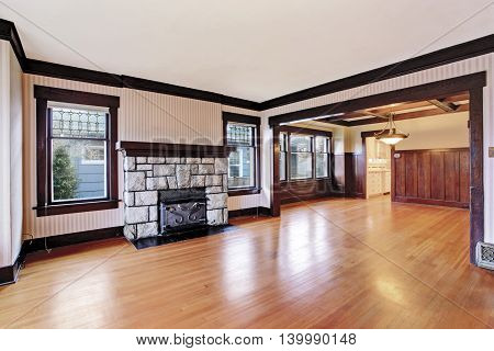 Empty Family Room With Antique Stone Fireplace And Hardwood Floor.
