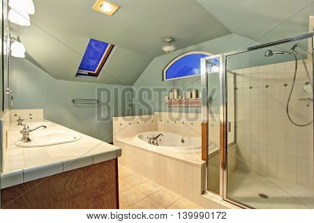 Old Ivory Bathroom With Vaulted Ceiling And Skylights.