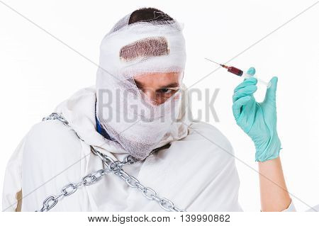 Young insane man with straitjacket and chains preparing for an injection - isolated on white.