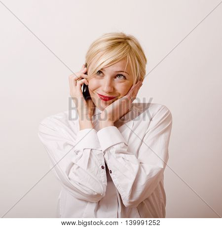 young cute real girl talking on phone against white background, lifestyle people concept isolated