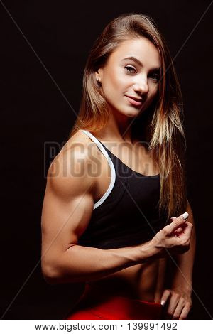 Image Of Muscular Young Woman Posing In Sportswear Against Black Background. Fit Female Model With P