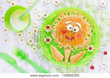 Baby pancakes for breakfast. Creative idea for the kid dessert: delicious pancakes in the form of flower with fruit and berry on white background
