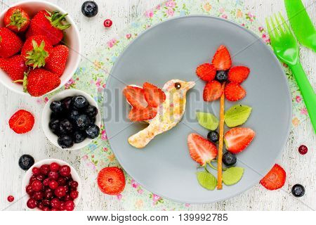 Creative idea for the kid's breakfast or dessert - flower of fresh strawberries kiwi and blueberries and toast with butter and sugar shaped bird hummingbird. Cute summer food edible picture on plate