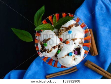 Ice cream decorated with chocolate syrup and mint in a glass. top view