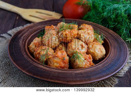 Meat balls with greens in a clay bowl.