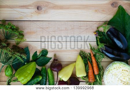 Freshly picked vegetables and herbs on a wooden background. top view