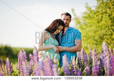 Happy Pregnant Couple At Sunny Day Near Violet Flowers