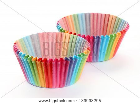 Colourful rainbow paper baking cases isolated on white background