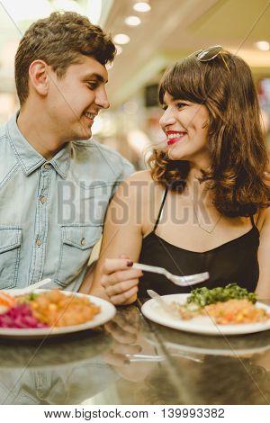 Young couple sitting in a restaurant eating a meal and looking at each other eyes