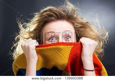 Blonde girl with blue eyes hiding after a cardigan