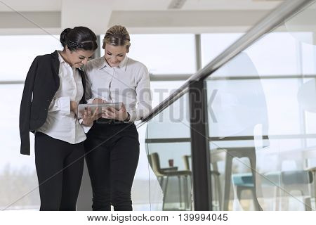 Two business colleagues standing in a modern office building hallway on a coffee break