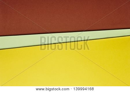 Colored cardboards background in brown green yellow tone. Copy space. Horizontal