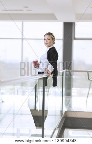 Young successful business woman standing in an office building hallway holding a cup of take away coffee