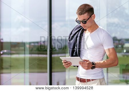 Young fashionable wearing a freelancer working on the tablet.