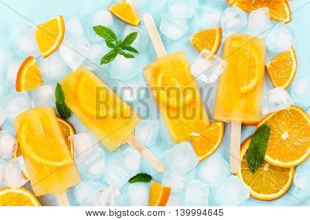 Fruit Orange Ice Lolly And Ice Cubes And Slices Of Orange On Blue Background.